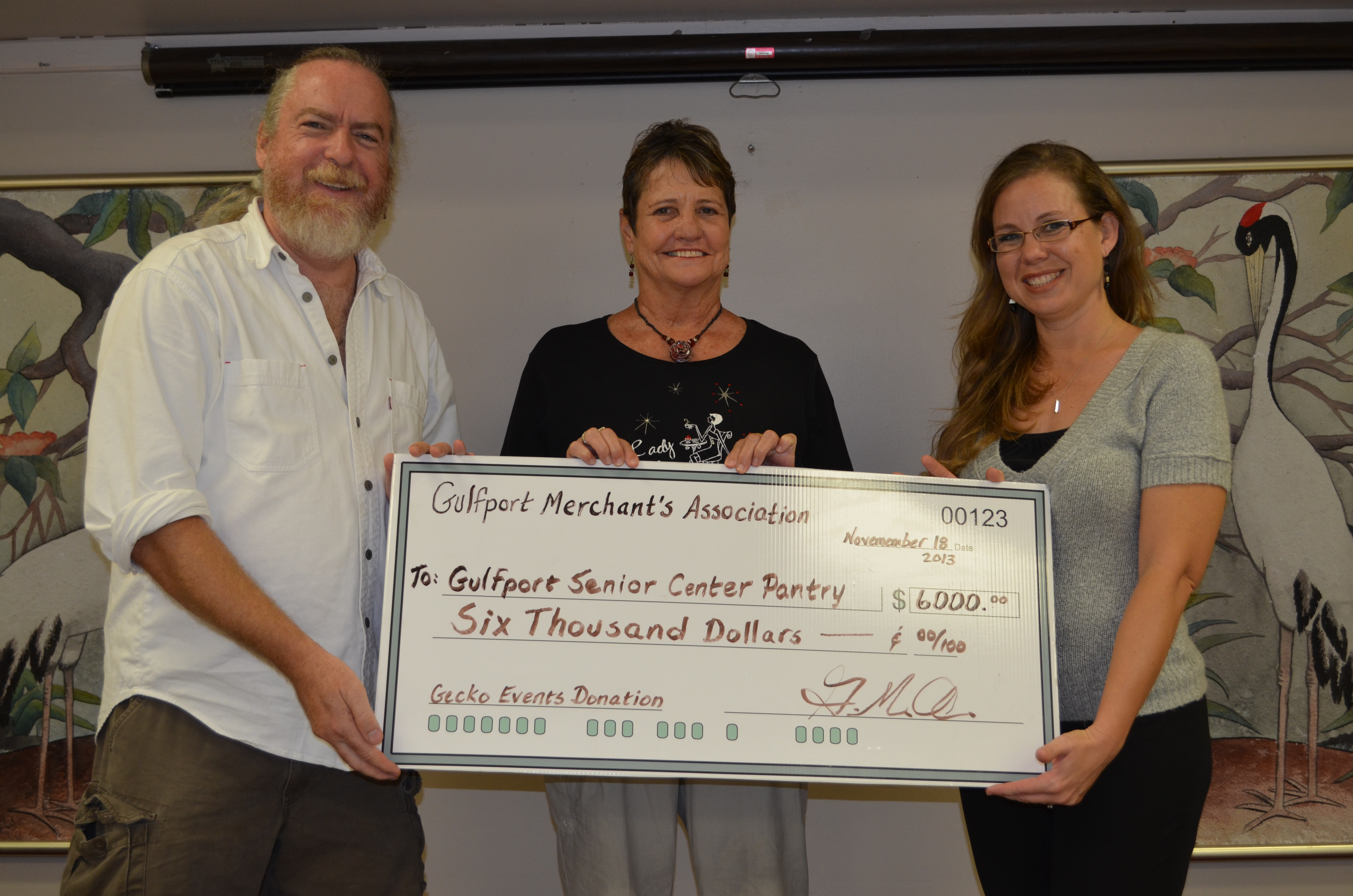 Gulfport Merchants Association Board (GMA) members Daniel Hodge (left) and Marsha Warner (center) present a donation to Rachel Cataldo, Gulfport Senior Center Coordinator, representing $6,000 worth of food and supplies to be donated to the Senior Center Pantry.